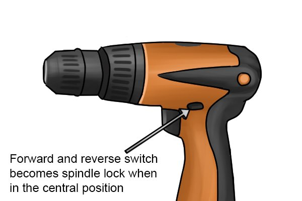 Reverse/forward button on a cordless drill driver as a spindle lock