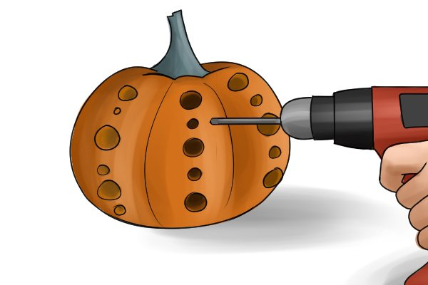 Drilling different sized holes into a pumpkin with a cordless drill driver