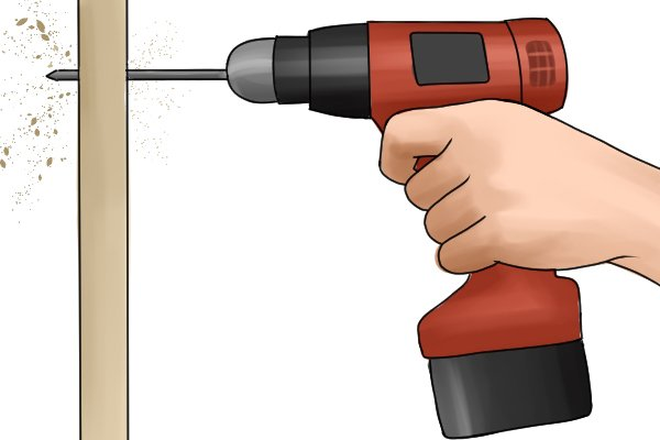 Holding a cordless drill driver by two hands to drill a hold in wood