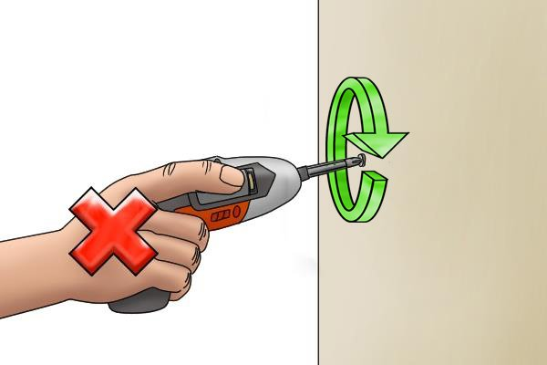 Cordless screwdriver in use with cross through it