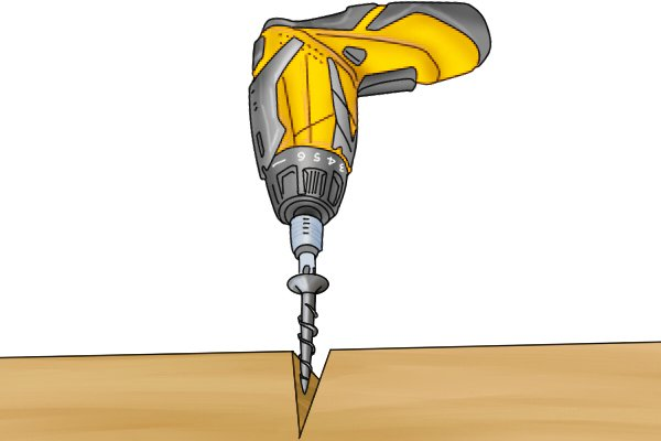 Cordless screwdriver drilling into a piece of wood
