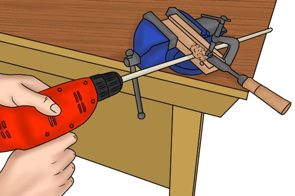 Fixing wooden strip into a power drill so that it can be rotated as it is pushed through a hole in a metal plate to create a dowel rod