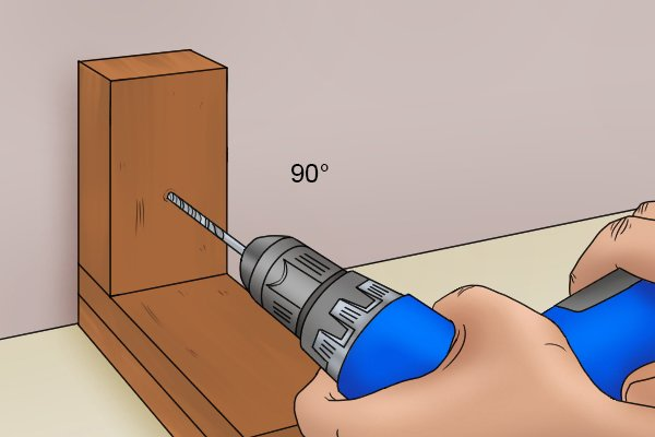 Drill press drilling a dowel hole perpendicular to the wood surface