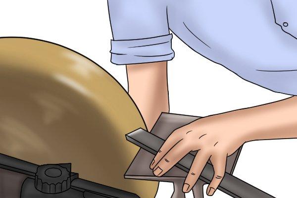 Sharpening an engineers scraper on a grinding wheel