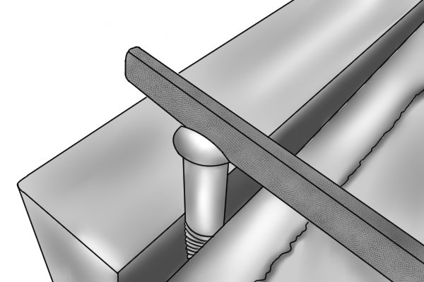 Image of a slotting file creating the slot in a screw head