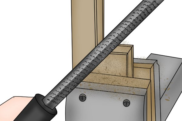Image of a DIYer using a square rasp to smooth off an internal right angle in their woodworking project