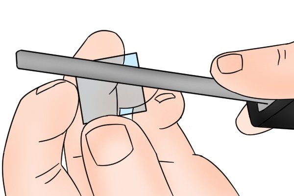 A DIYer using a diamond file to shape a piece of glass