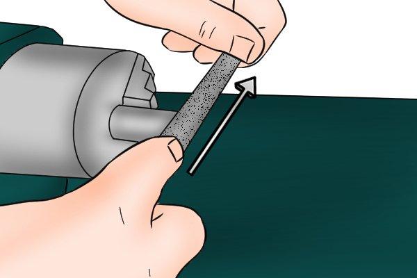 Image of a DIYer demonstrating lathe filing