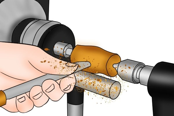 Image of a wood turning chisel being used to shape a piece of wood on a lathe