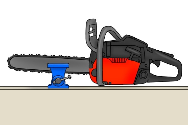 Image showing a chainsaw secured in a vice by the blade