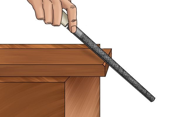 Image of a DIYer putting a bevel on a piece of wood by cross filing it with a rasp