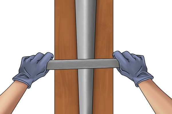 Image of a DIYer draw filing a bevel on a piece of metal
