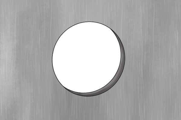 Image of a round hole cut into a piece of steel