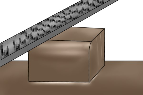 A DIYer filing the corner off a piece of metal to leave a smooth, rounded finish