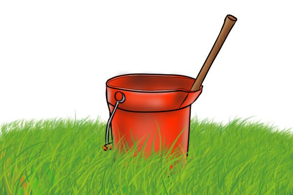 Mattock being soaked in a bucket of water to tighten the hold of the handle on the head