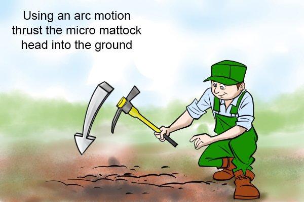 Using a micro mattock, Using an arc motion thrust the micro mattock head into the ground