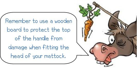 """Wonkee donkee advice says """"Don't forget to use a wooden board to protect the handle when removing and replacing the head of your mattock."""""""