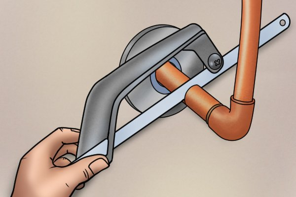 Using a hacksaw to cut pipe