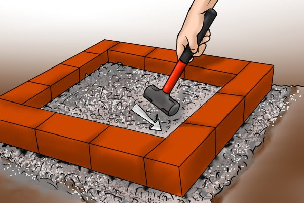 Using a paver's maul to gently tap bricks into place