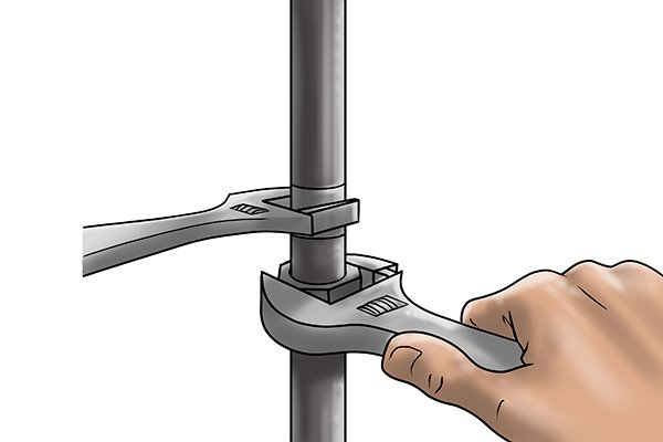 Using two adjustable spanners to tighten a pipe fitting