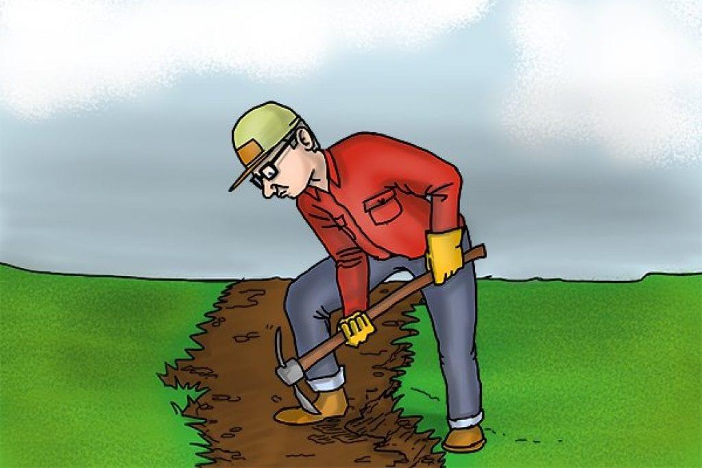Man using adze to dig