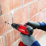 Hilti SF 6H-A22 Cordless Hammer Drill Driver 3 drilling through a brick wall by a masonry worker