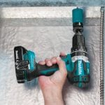 Makita cordless hammer drill cutting through metal