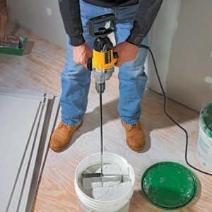 Mixing plaster with Dewalt mixer drill.