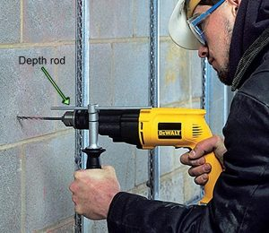 Dewalt percussion drill being used with depth rod.