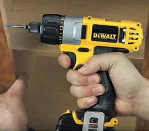 Squeezing trigger on Dewalt cordless screwdriver.