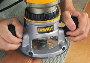 Using Dewalt hand router on a wooden material.